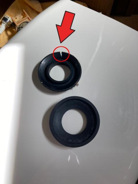 【画像】新しい密結パッキンと古い密結パッキンを比較しています。上に置いてあるものが古い密結パッキンです。ゴム部分がパックリ割れています。